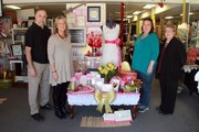three women and one man pictured together with a valentine's day display